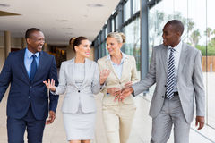 Multiracial businesspeople walking together. Beautiful multiracial businesspeople walking together in office building Stock Image