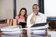 Multiracial businesspeople working on documents. African American businessman and Indian businesswoman meeting in office boardroom with stacks of documents Royalty Free Stock Photos