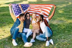 multiracial cheerful friends with american flag sitting on green grass stock photography