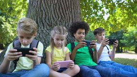 Multiracial children company playing games on gadgets sitting under tree in park