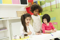 Multiracial children drawing in the playroom Stock Image
