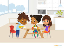 Multiracial children preparing lunch by themselves and eating. Two girls sitting at table and boy pouring orange juice into glass. Stock Photos
