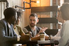 Multiracial colleagues discussing ideas during work break in caf royalty free stock image