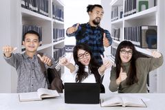 Multiracial students showing thumbs up in the library. Multiracial college students studying together while showing thumbs up in the library Stock Images