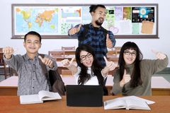Multiracial college students with thumbs up. Image of multiracial college students looks happy in the classroom while giving thumbs up at the camera Royalty Free Stock Photos