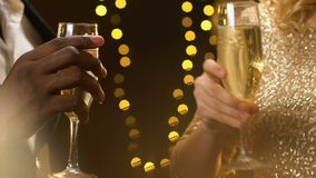 Multiracial couple clinking champagne at new year party, lights glowing, closeup. Stock footage stock video footage