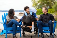 Multiracial couple with disabled boy in wheelchair outdoors by l stock image
