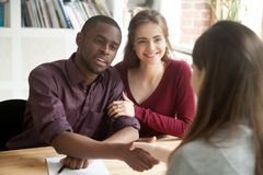Multiracial couple excited with successful house purchase deal. Excited multiethnic couple of Caucasian wife and black husband happily looking at real estate stock image