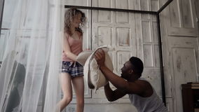 Multiracial couple have fun in the morning. Man and woman in pajamas have fight with pillows. Slow motion. stock video