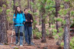 Multiracial couple hiking in fall forest. Multiracial group of hikers in forest. Couple hiking in autumn in nature outdoors. Asian women hiker in front smiling stock photography