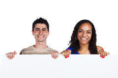 Multiracial couple holding a blank banner. Young african women and caucasian men holding a blank white placard (isolated on white Royalty Free Stock Photography