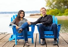 Multiracial couple in late forties on blue chairs by lake stock image