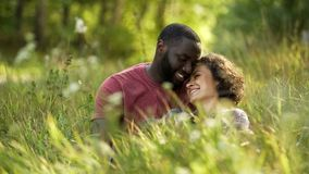 Multiracial couple laughing and chatting while lying in grass, outdoor date. Stock photo stock photography