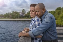 A multiracial couple looks over the pier stock photography
