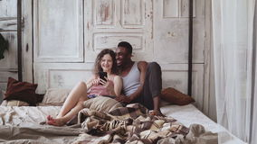 Multiracial couple in pajamas sitting on bed and use smartphone. African man and european woman looking photos, laughing Stock Photo