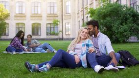 Multiracial couple relaxing on grass, hugging and smiling, first love, students royalty free stock photos