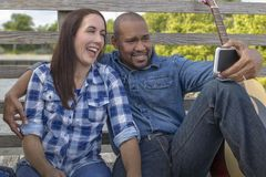 A multiracial couple sits on a deck laughing royalty free stock images