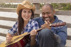 A multiracial couple sits on a deck playing guitar royalty free stock photo
