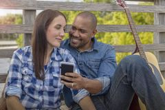 A multiracial couple sits on a deck reviewing selfies stock photography