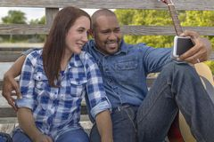 A multiracial couple sits on a deck with smartphone stock photos