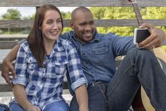 A multiracial couple sits on a deck taking a selfie royalty free stock photos