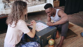 Multiracial couple sitting on the floor in pajamas and playing the board game together. Man throw the dice and take card Stock Photos