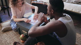 Multiracial couple sitting on the floor in pajamas and playing the board game together. Man throw the dice and take card Stock Photo