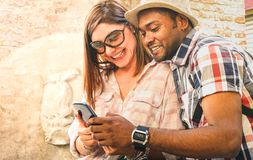 Multiracial couple using mobile smart phone at old town trip - Fun concept with alternative fashion travelers - Indian boyfriend. With caucasian girlfriend royalty free stock images