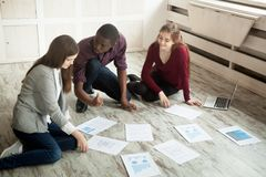 Multiracial creative team brainstorming at office floor. Multiracial creative business team brainstorming discussing visual handouts on floor. Designers stock images