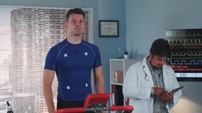 Multiracial doctor increasing speed on the treadmill during the athlete stress test. In cozy modern sports lab stock footage