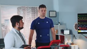 Multiracial doctor telling athlete about something during stress testing. In sports lab with scyscrapers in the background. In Scientific Sports Laboratory stock video footage