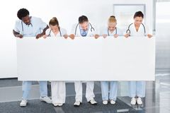 Multiracial doctors holding placard. Group Of Happy Multiracial Doctors Holding Placard In Clinic Stock Image