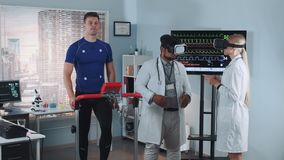 Multiracial doctors in virtual reality glasses speaking about something and gesturing during stress test. The athlete walking on racetrack. In Scientific stock footage