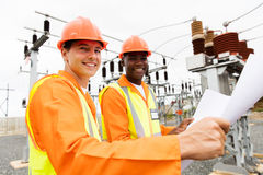 Multiracial electricians blueprint royalty free stock photos