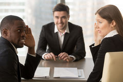 Multiracial employers hiding faces, discussing job applicant, ba. Multiracial confused employers covertly discuss job applicant, hide face with hands, look Royalty Free Stock Images
