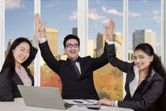 Multiracial entrepreneurs clapping hands at workplace Stock Images
