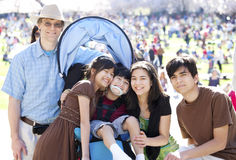 Multiracial family in crowd with disabled child in wheelchair stock photo