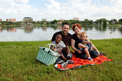 Multiracial family have picnic. By a lake Royalty Free Stock Images