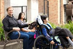 Family with special needs child sitting outdoors together in sum stock image