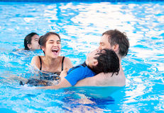 Multiracial family swimming together in pool. Disabled youngest Royalty Free Stock Photos