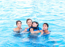 Multiracial family swimming together in pool. Disabled youngest Stock Photography