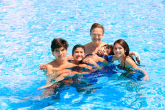 Multiracial family swimming together in pool. Disabled youngest. Son has cerebral palsy Royalty Free Stock Images