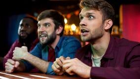 Multiracial fans celebrating favorite team scoring goal, watching game in pub. Stock photo stock photo