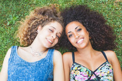 Multiracial female couple of friends lying on the grass Stock Photography