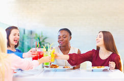 Multiracial female friends having fun in restaurant Stock Photography