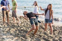Multiracial Friends at Beach. Friends Dancing Limbo at Beach Stock Image