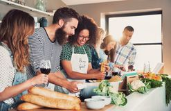 Multiracial friends cook tasteful food. Multiracial funny friends cook some tasteful food at kitchen while drinking wine Royalty Free Stock Photography