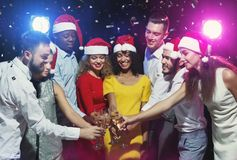 Multiracial friends drinking champagne at New Year party. Multiracial friends drinking champagne during New Year party celebration stock photo