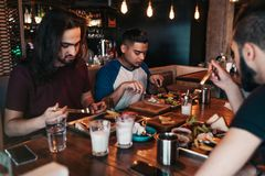 Multiracial friends eating breakfast in cafe. Young men chat while having tasty food and drinks. Guys hangout together. Multiracial friends eating breakfast in Stock Photography
