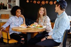 Multiracial friends eating in a cafe Stock Image